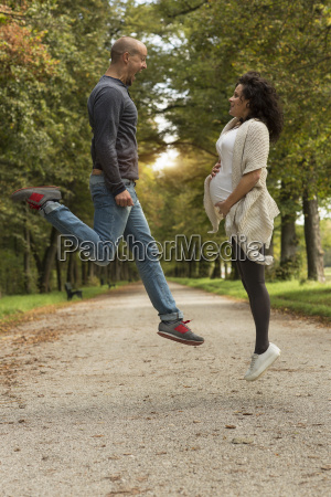 pregnant couple jumping face to face