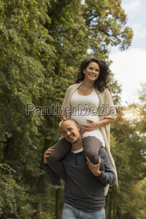 pregnant couple playing piggyback in park