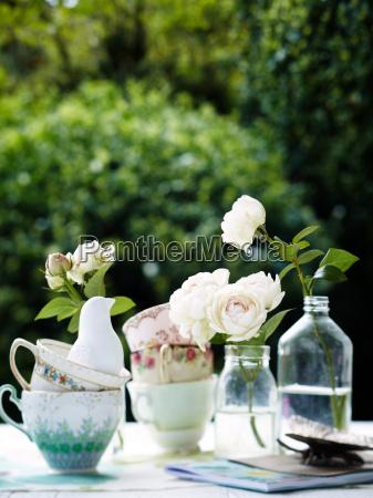 flowers in vintage bottles with teacups