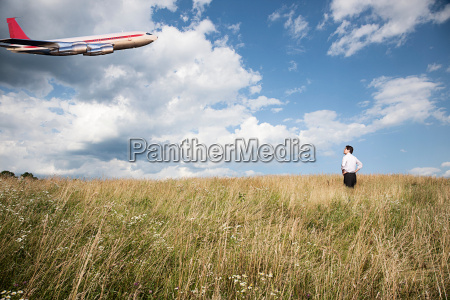 businessman in field looking at airplane