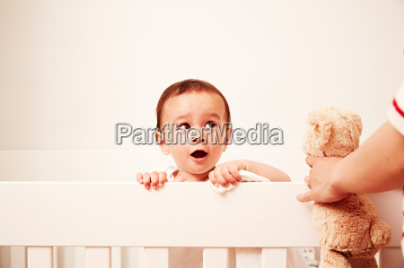 baby looking over crib looking at
