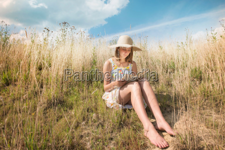adolescent girl in sunhat reading story