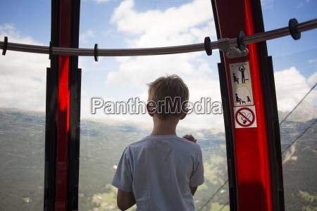 boy looking out from cable car
