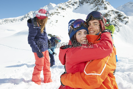 friends wearing skiwear hugging kuhtai austria