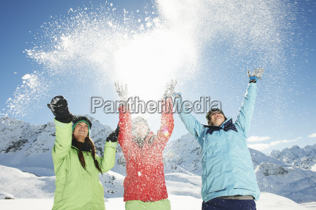 female, friends, throwing, snow, mid, air, - 19512950