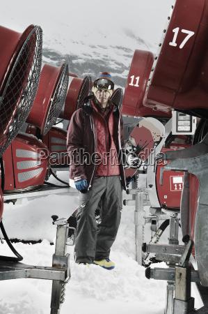 young man standing among snowmobiles