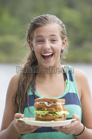 portrait of teenage girl holding sandwich