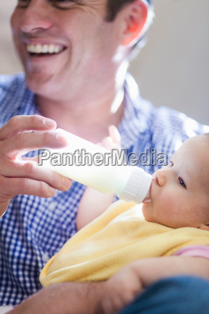 father feeding baby daughter bottle