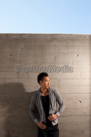 man leaning on concrete wall