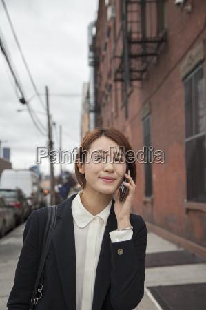 businesswoman using smartphone on street