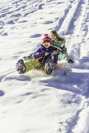 girls riding sled down snow covered