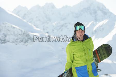 young man holding snowboard kuhtai austria