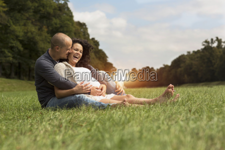 pregnant couple sitting on grass in
