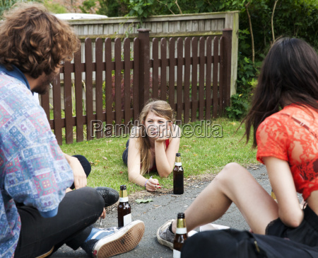 friends sitting in garden drinking beer