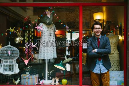 man standing by doorway of shop