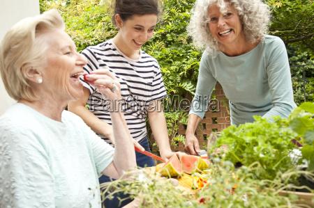 three women preparing food at garden