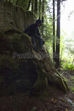 boy sitting on tree stump