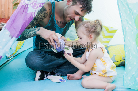 young man and toddler daughter playing