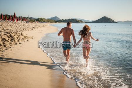 young couple running in sea castiadas