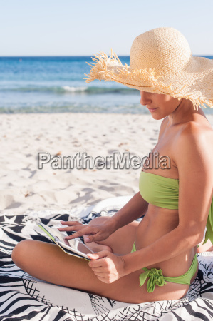 woman using tablet computer on beach