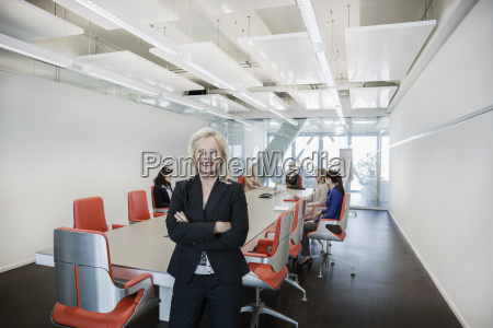 mature woman in office with colleagues