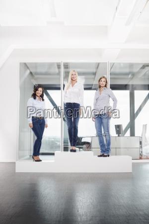 three women on podium in office