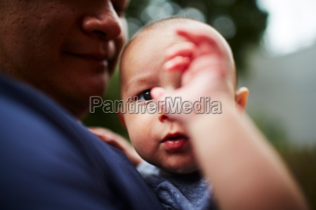 father holding baby son close up