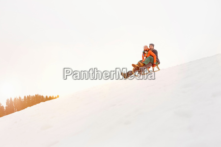 couple on toboggan in snow