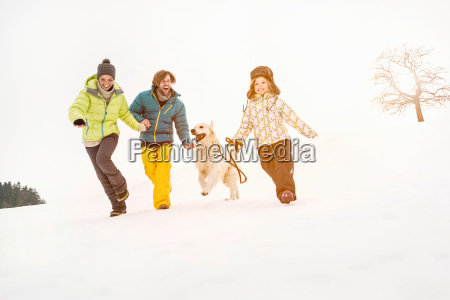 family running on snow with dog