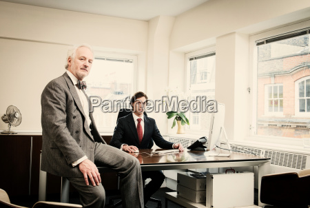young businessman at desk with senior