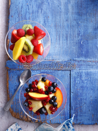 schuesseln fruchtsalat auf hoelzernem brett