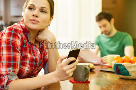 young couple at breakfast woman using