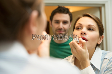 young woman applying lipstick in bathroom