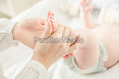mother holding baby boys feet close