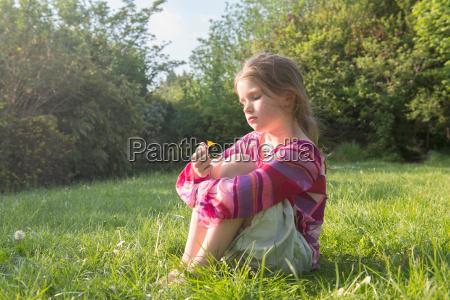 girl sitting in grassy field