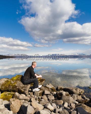 man admiring still rural lake