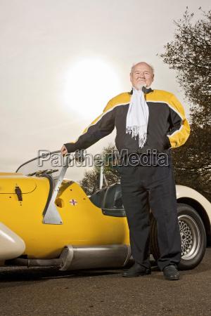 older man standing with custom car
