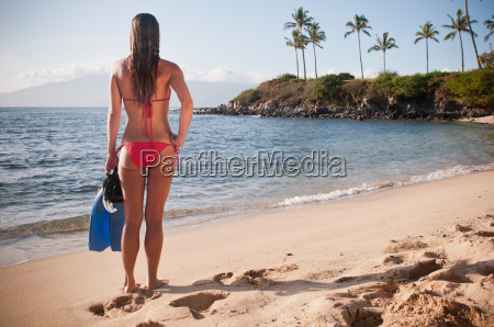 woman carrying fins on tropical beach
