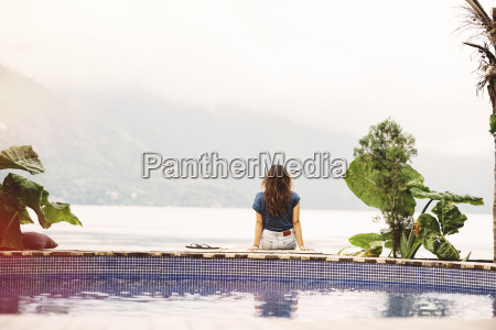 young woman sitting on edge of