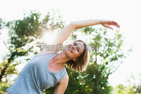 smiling woman stretching outdoors
