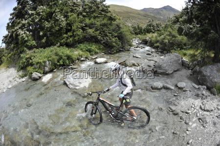 woman pushing mountain bike through water
