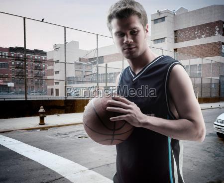 man carrying basketball on city street