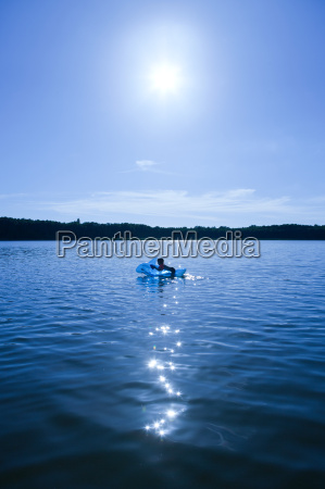 boy swimming in lake with an