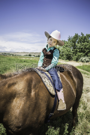girl wearing cowboy boots and hat