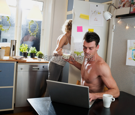mid adult couple using laptop in