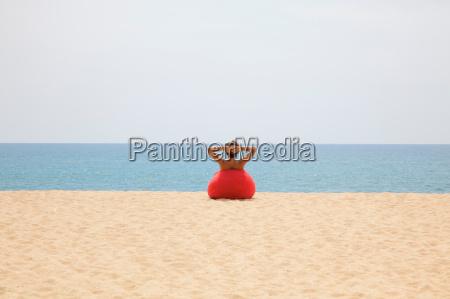 man relaxing in beanbag on beach