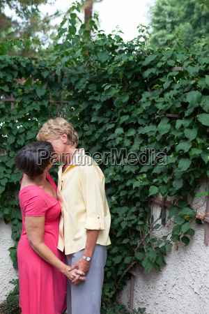 mature lesbian couple kissing in garden