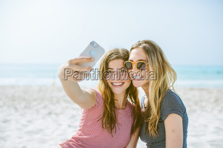 two young female friends taking smartphone