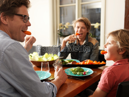 father and sons sitting at table