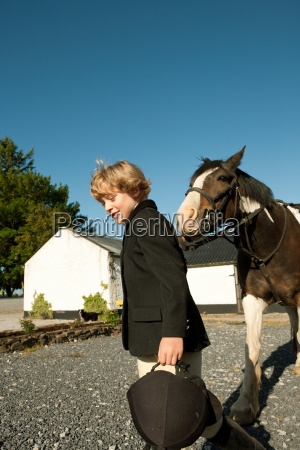 boy walking with horse